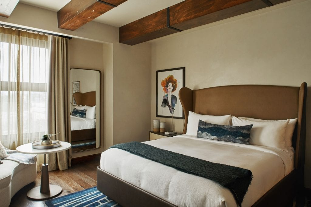 hotel room with king bed, chair and table