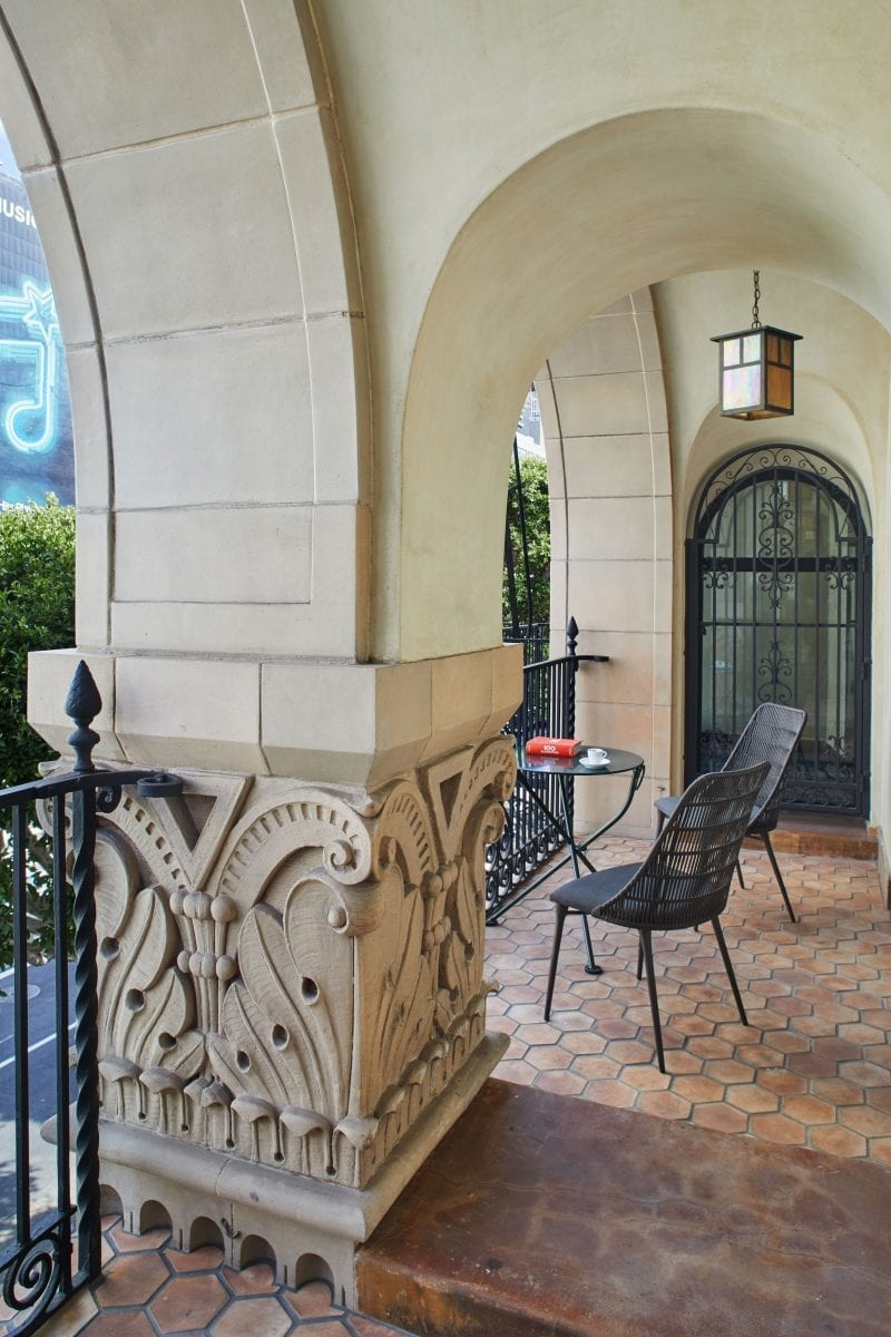 an exterior hallway with patio furniture