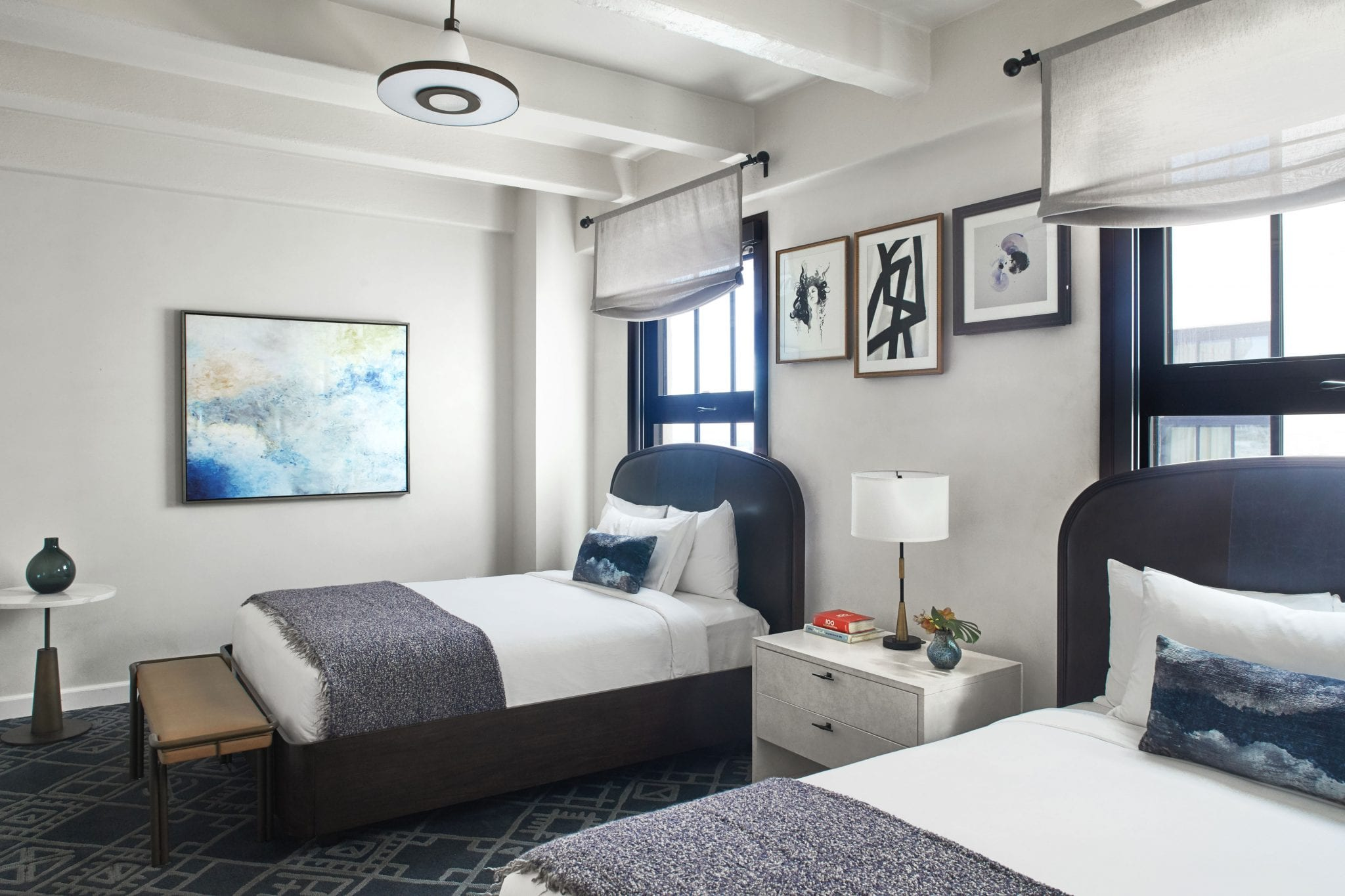 hotel room with two beds, nightstand and framed art