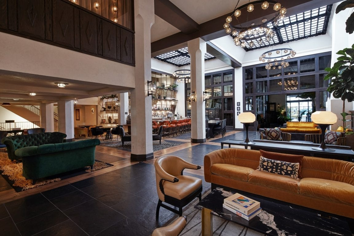 hotel lobby with sofa, chairs, high ceiling and bar in the background