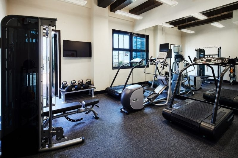exercise room with treadmill, stationary bikes and weights