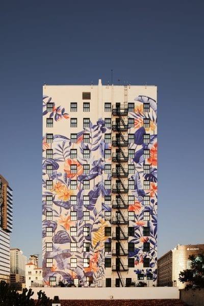 back of a building painted with colorful mural by Bella Gomez