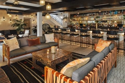 bar with lounge area with sofas, coffee table, and bar with high chairs