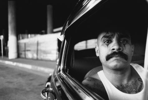 man with clown tattoos around eyes sitting on a car, looking out a window