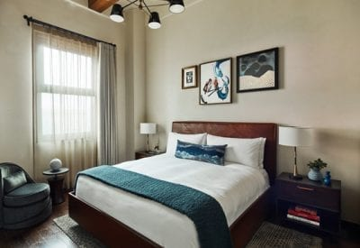 hotel room bed, nightstands, chair and small table