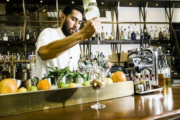 a man standing behind a bar preparing a fruit cocktail