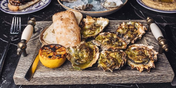 cutting wood board with grilled oysters, lime and toasted bread